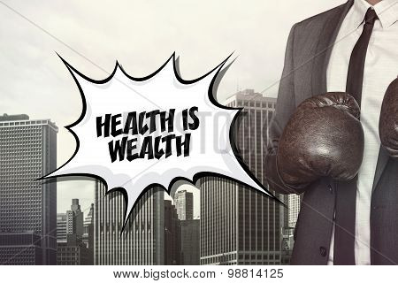 Health is wealth text with businessman wearing boxing gloves