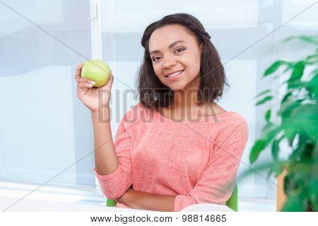 Beautiful mulatto woman holding apple