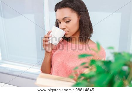 Attractive mulatto lady drinking tea and reading book