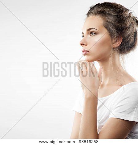 Studio portrait of profile of a pensive girl in white shirt