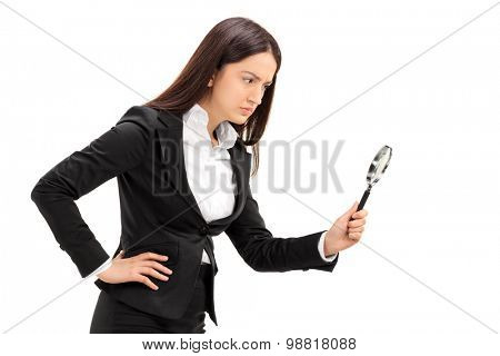 Businesswoman looking through a magnifying glass isolated on white background