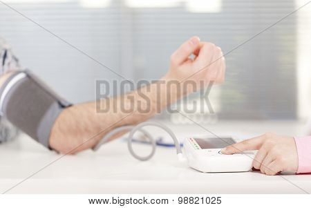 Female doctor checking patient blood pressure
