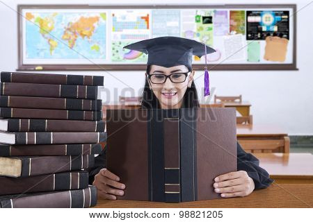 Beautiful College Student With Mortarboard Reads Book