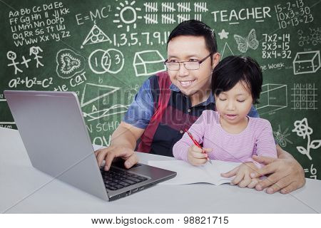 Elementary School Student Learning With Tutor In Class