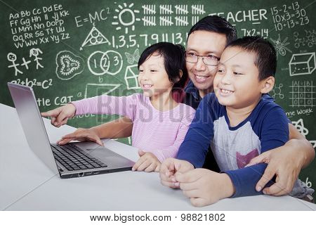 Elementary School Teacher Using Laptop With Students