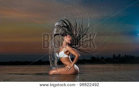 Sexy brunette woman in wet white swimsuit posing in river water with sunset sky on background
