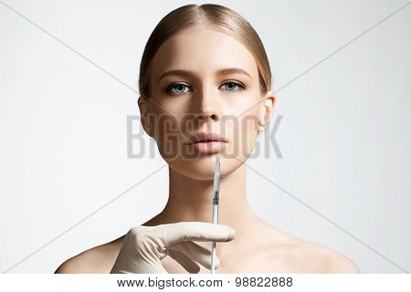 Woman doing an injection to increase the lips
