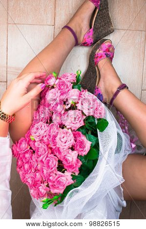 Stylish woman with pink roses. Top view