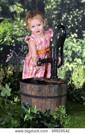 An adorable 2 year old looking up as she feels inside the spigot of an old water pump.