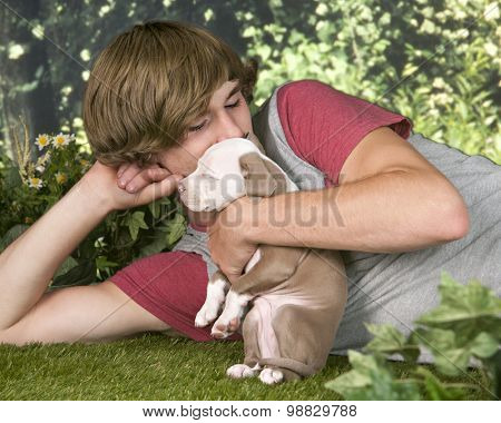 A teen boy laying on a summer lawn while cuddling his tiny pit bull pup.