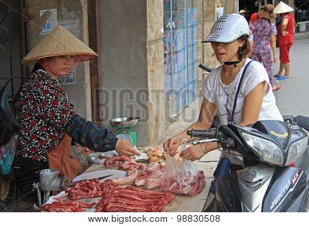 woman is buying some pieces of meat