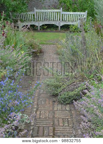Garden Pathway Leading To A Curved Bench