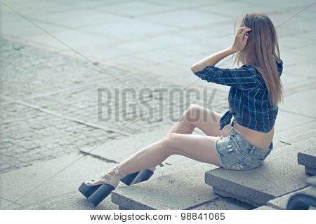 Stylish Girl In Shirt And Denim Shorts Sitting On The Steps.