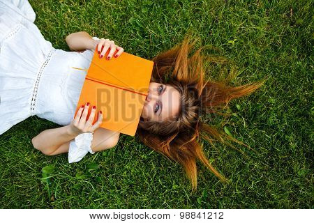 Girl Hides Her Face Behind Book Lying On Lawn.