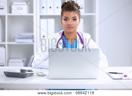 Female doctor sitting on the desk and working a laptop