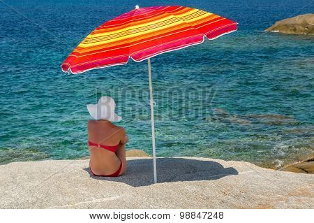 Woman In Red Bikini And White Hat Under Parasol Looking Out To Sea