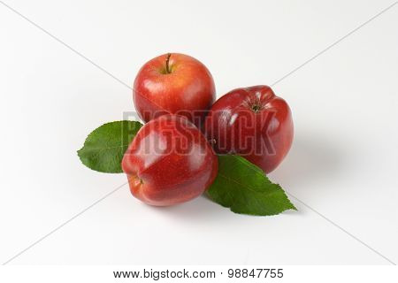 red apples with leaves on white background