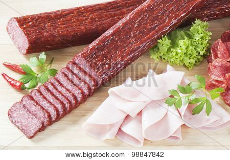 sliced salami and ham on wooden cutting board