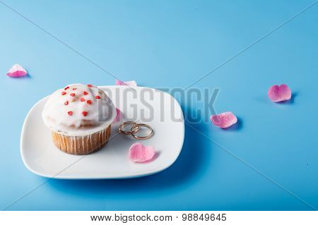 Colorful Muffin On Saucer With Flower Petal And Wedding Rings