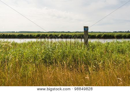 Wooden Pole With A Figure On The Bank Of A Small River