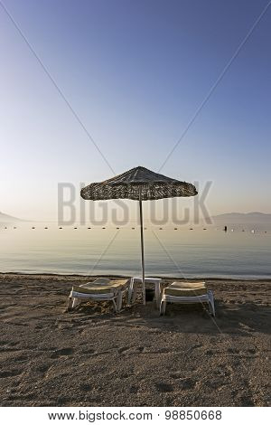 Sun Loungers And Sunshade On Beach
