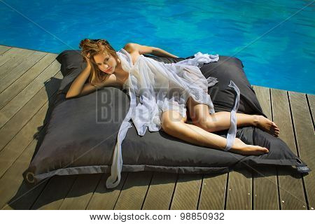beautiful girl relaxing on a huge pillow near the pool