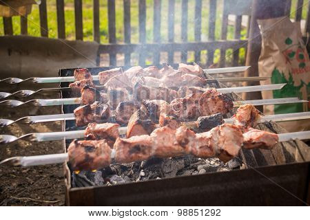Six skewers smoke from a semi-meat on the grill