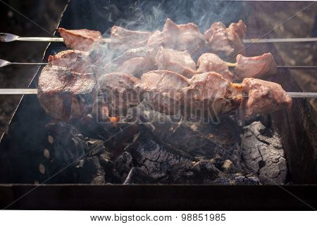 Semi-finished meat on skewers in the smoke of grill