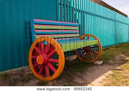 Unusual multicolored bench of the wheels in village