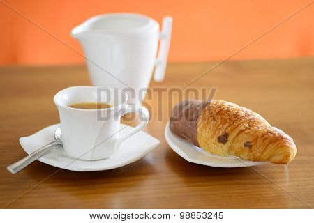 Cup of coffee, croissant and a milk jug
