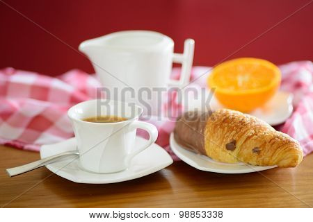 Cup of coffee, croissant, orange and a milk jug