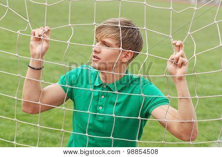 Young Man Looking Through Net Soccer Football Goal Catch