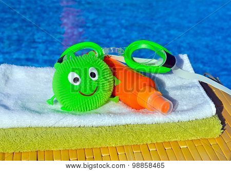 Bath Towels, Goggles And Sun Spray, Toy Against Blue Water