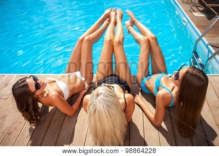 Beautiful young women are sunbathing near water