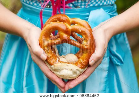 Oktoberfest Pretzels In Hands Of A Woman In Traditional German Clothes, Blue Bavarian Dirndl. Bread