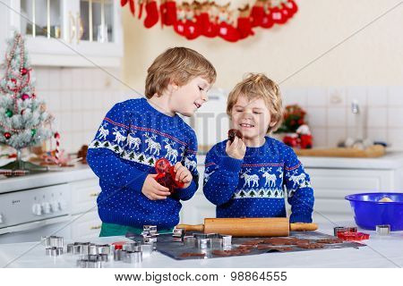 Two Little Boys Baking Gingerbread Cookies In Domestic Kitchen