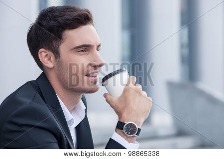 Handsome young businessman is enjoying hot drink outdoors