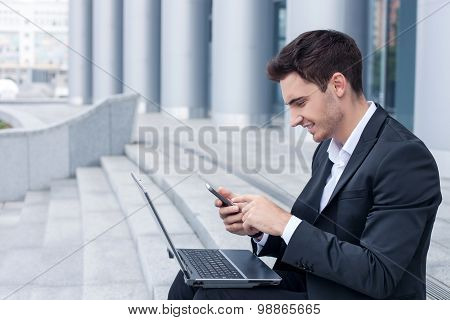 Attractive young businessman is using modern technology