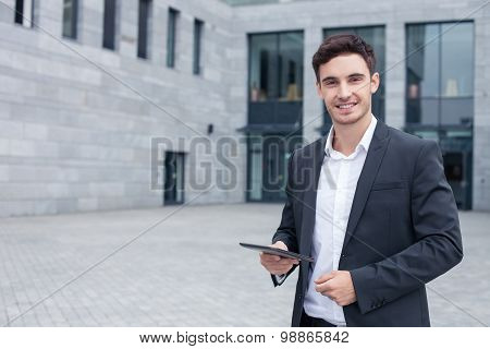 Cheerful young businessman is using modern technology