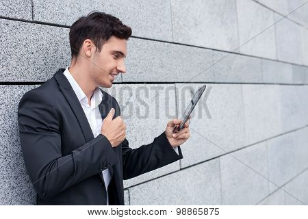 Handsome young businessman is using modern technology