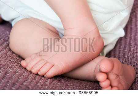 beautiful newborn baby's legs on a soft blanket