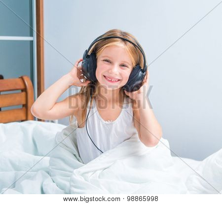 little girl listening to music at home in white bed