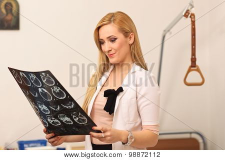 Portrait Of A Smiling Female Doctor Sitting At Work