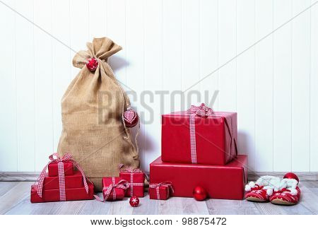 Christmas presents wrapped in red paper with checked ribbon on white wooden background.