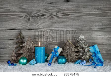 Blue, white and grey Christmas decoration with one burning candle for the first advent.