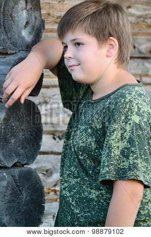 Teen Boy in camouflage stands near wooden wall