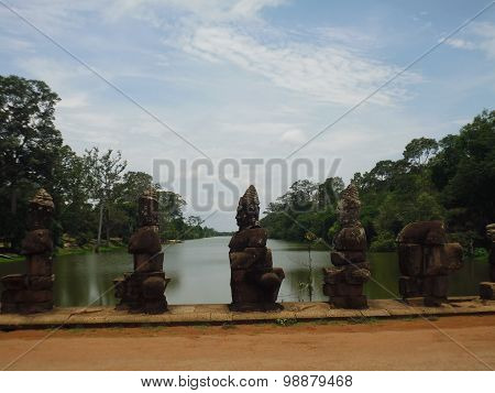the statues on the bridge over the pond in the Agkor