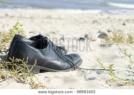 Black Men's Shoes Standing On The Sandy Beach, Vacation Background