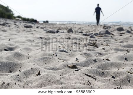 Blurred Silhouette Of A Man Walking On The Beach