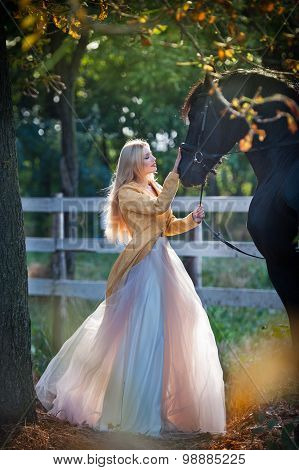 Fashionable lady with white bridal dress near black horse in forest. Beautiful young blonde woman
